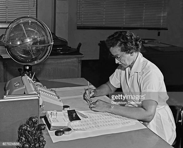 NASA space scientist and mathematician Katherine Johnson poses for a portrait at her desk with an adding machine and a 'Celestial Training device' at...