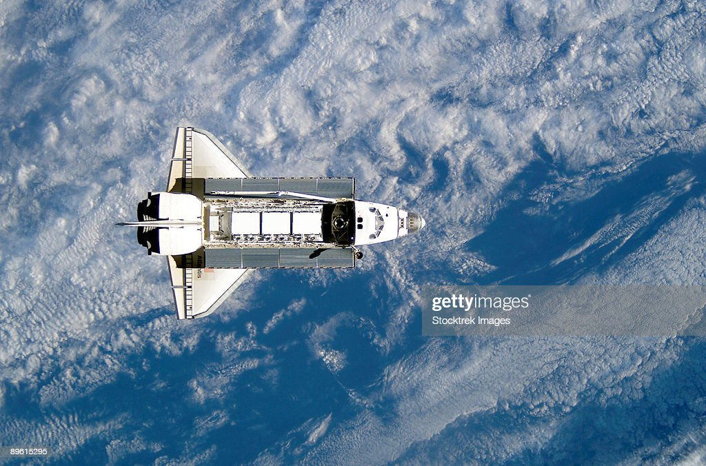 Space Shuttle Atlantis backdropped against a blue and white Earth.