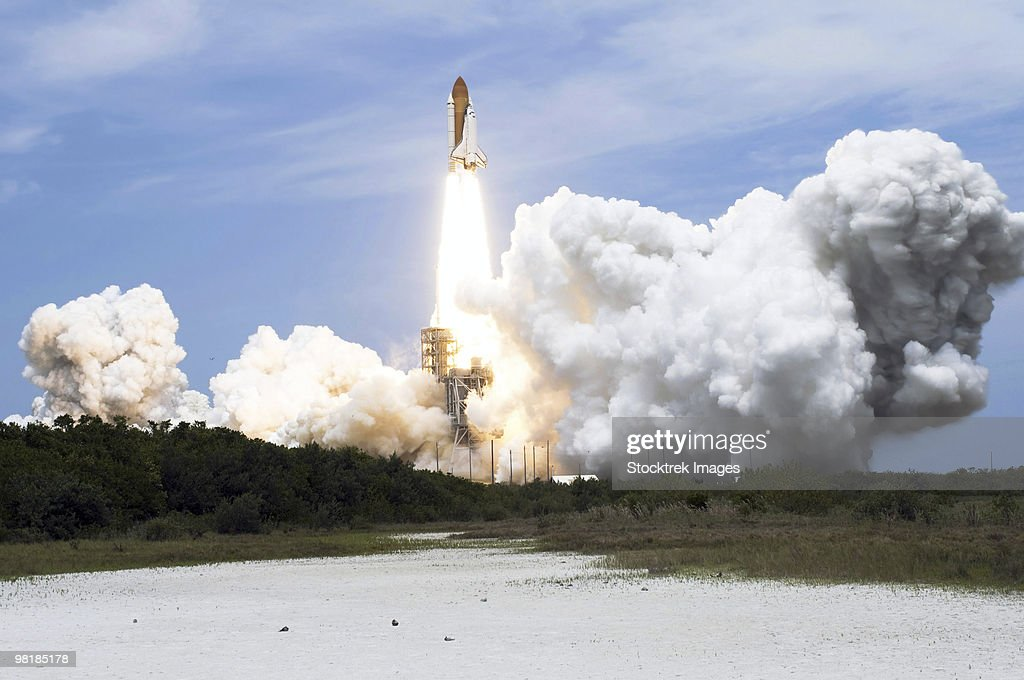Space Shuttle Atlantis lifts off from its launch pad toward Earth orbit.