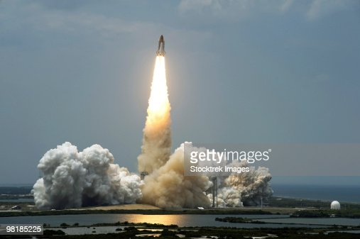 Space Shuttle Atlantis lifts off into the sky.