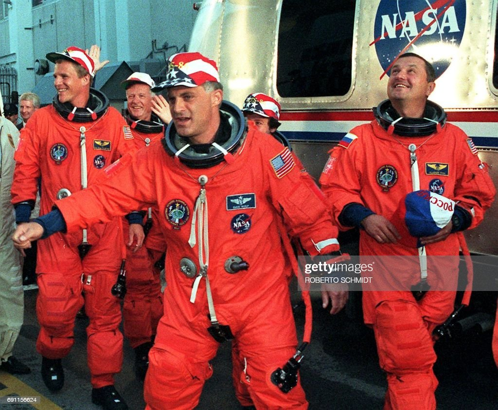 US space shuttle Atlantis US crew member Dave Wolf (C) acknowledges wellwishers prior to boarding the Astrovan 25 September with US astronaut Scott Parazynski (L), Frenchman Jean-Loup Chretien (Rea...