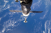 February 26, 2011 - Backdropped by a blue and white part of Earth, space shuttle Discovery approaches the International Space Station during STS-133 rendezvous and docking operations. A Russian Progre