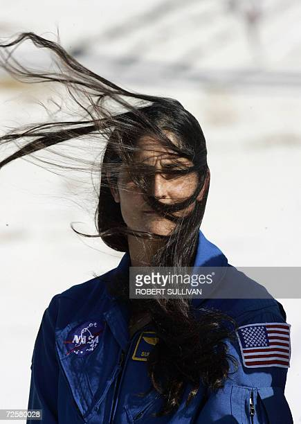 US space shuttle Discovery crew member Sunita Williams has her face covered by her windblown hair during a press conference conducted at the launch...