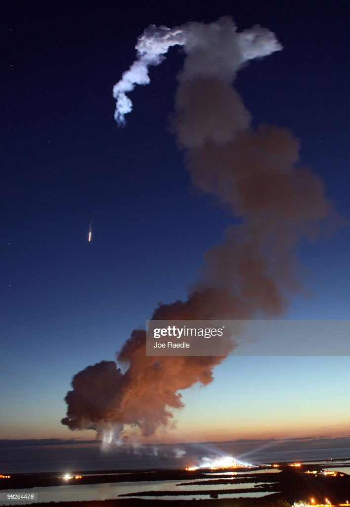 Space Shuttle Discovery is seen streaking into space (to the left) as a plume of smoke floats through the air after it blasted off from launch pad 39-A at the Kennedy Space Center on April 5, 2010, in Cape Canaveral, Florida. Discovery is scheduled for a 13 day mission to the International Space Station.
