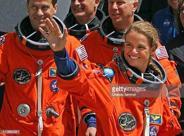 Space shuttle Endeavour astronaut Julie Payette of the Canadian Space Agency waves to supporters with small Canadian flags as the crew of seven...