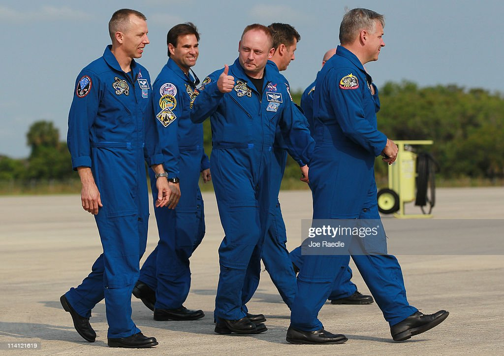 Space shuttle Endeavour astronaut Michael Fincke gives a thumbs up as he walks with crew members Andrew Feustel (L), Greg Chamitoff (2nd L), and pilot Gregory Johnson (R) after their arrival at Kennedy Space Center on May 12, 2011 in Cape Canaveral, Florida. Space shuttle Endeavour is scheduled to launch on its final flight to the space station on May 16th.
