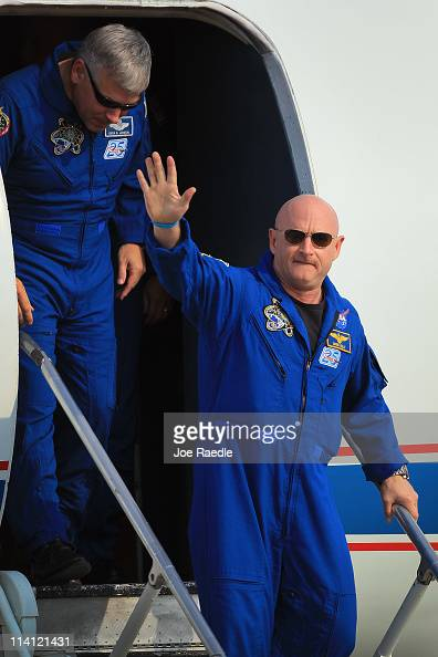 Space shuttle Endeavour crew Commander Mark Kelly waves as he walks off a plane with Pilot Gregory Johnson after arriving at Kennedy Space Center on...