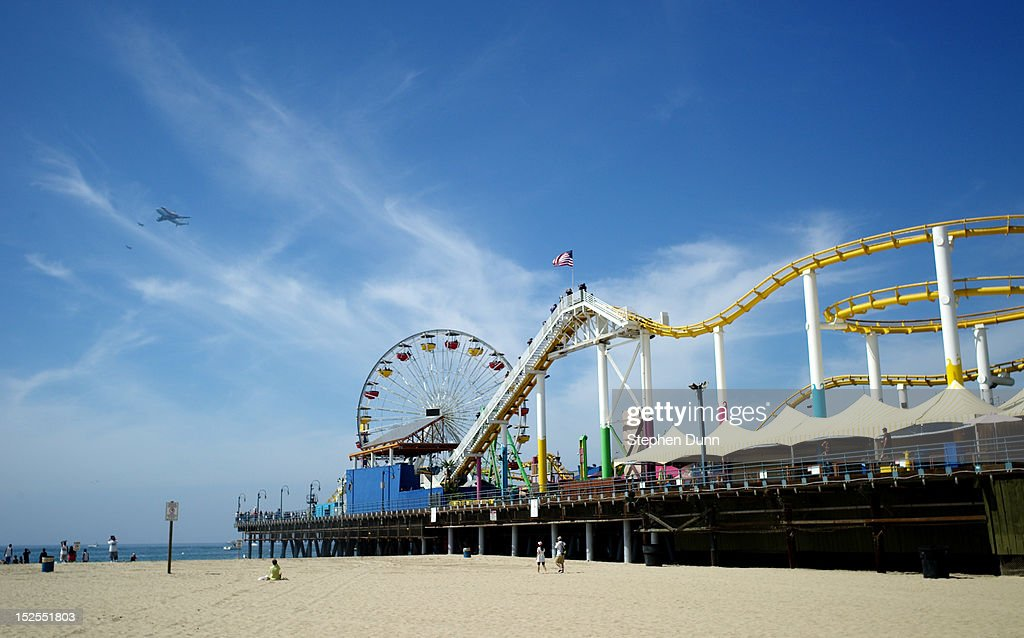 Space shuttle Endeavour sitting on top of NASA's Shuttle Carrier Aircraft or SCA flies past Santa Monica Pier on September 21 2012 in Santa Monica...