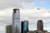 Space shuttle Enterprise mounted atop a 747 shuttle carrier aircraft flies past the Jersey City skyline prior to landing at John F Kennedy...