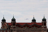 Space Shuttle Enterprise mounted atop a 747 shuttle carrier aircraft flies past Ellis Island prior to landing at John F Kennedy International Airport...