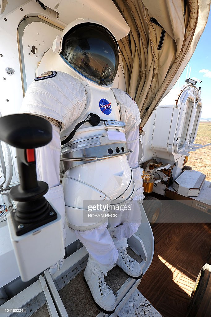 A space suit is mounted to a 'suit port' on the outside of NASA's newest rover prototype Space Exploration Vehicle (SEV), 15 September 2010 on the last day of NASA�s two-week field testing of new aerospace technology at Black Point Lava Flow in the north Arizona desert approximately 40 miles (64 km) north of Flagstaff, Arizona. The suit port will allow astronauts inside the SEV to climb into their suits and out of the rover in only 10 minutes, substantially cutting down on the current spacewalk preparation time of six hours. The testing program, called Desert Research and Technology Studies (Desert RATS), is an annual opportunity for NASA engineers and scientists to stress test rovers and other cutting-edge space technologies in an arid environment simulating the conditions found on the surface of the Moon, distant asteroids or Mars.