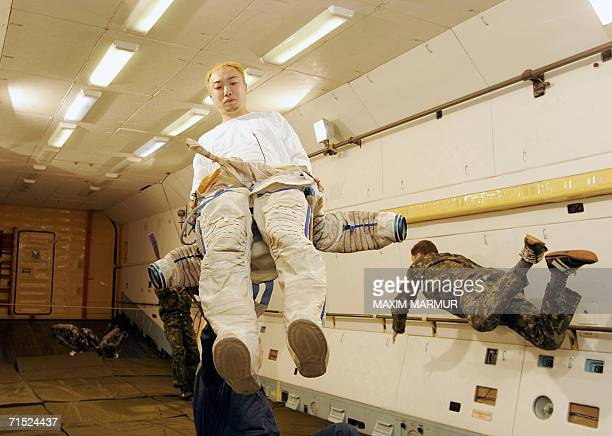 Space tourist Daisuke Enomoto of Japan tries to puts on a spacesuit inside a laboratory compartment where gravity is reduced to 00001g 810 sec and...