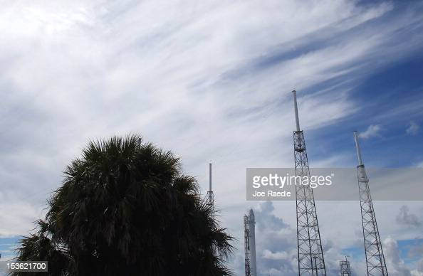 SpaceX Falcon 9 rocket attached to the cargoonly capsule called Dragon is seen surrounded lightning protection system towers as it sits on the launch...
