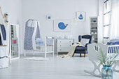 Vase next to white cradle in spacious baby's room with blanket on armchair and striped veil above crib