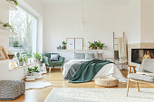 Spacious furnished bedroom interior with hed, fireplace, chair, armchair, rug and ornaments