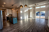 Wooden floors and high ceilings in a new home looking in toward the trendy kitchen.