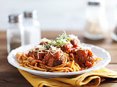spaghetti and meatballs with oregano garnish on rustic table shot with selective focus