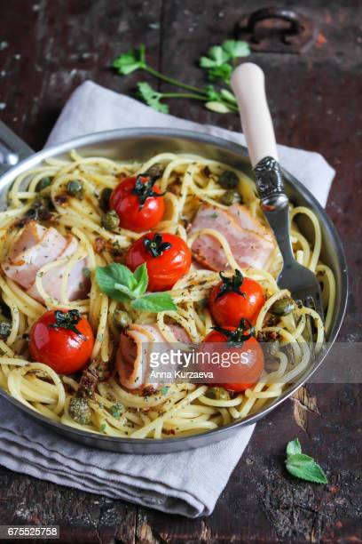 Spaghetti pasta with roasted cherry tomatoes, bacon slices, capers and herbs in a pan ready to serve, selective focus