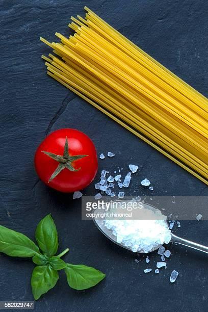 Spaghetti, tomato, and basil on a slate