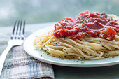 Spaghetti and home made tomato sauce on green plate