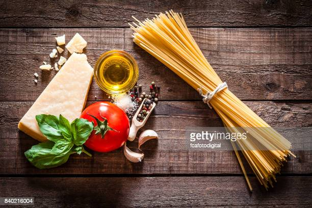 Spaghetti with ingredients on rustic wooden table