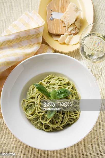 Spaghetti with pesto, parmesan and glass of white wine, close up