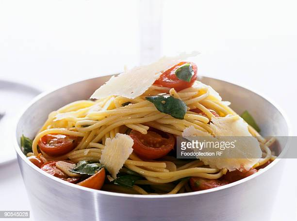 Spaghetti with spinach, tomatoes and Parmesan shavings, close up