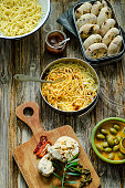 Spaghetti with tomato pesto, parmesan and selfmade buns of olives and tomatoes on a wooden board