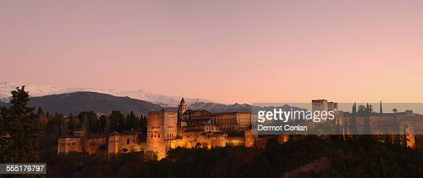 Spain, Andalucia, Granada, Alhambra, Cityscape with illuminated castle at dusk, pink sky