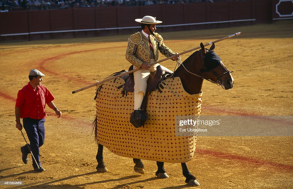 Spain Andalucia Seville Picador with lance riding a padded and blindfolded horse in the bullring at a bullfight in Arenal District