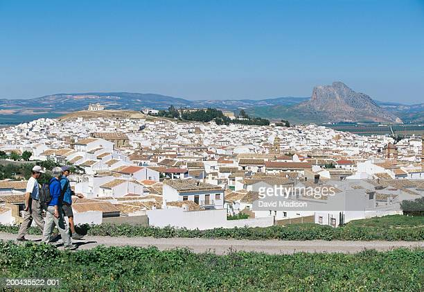Spain, Andalusia, Malaga, Antequera, three people walking, side view