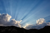 Spain, Andalusia, Natural Park of Cabo de Gata-Nijar, clouds and sunlight behind mountains