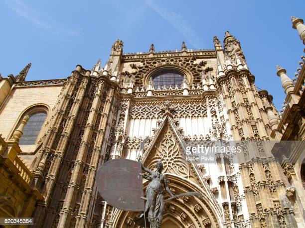 Spain, Andalusia, Seville, Cathedral with sculpture presenting faith in foreground