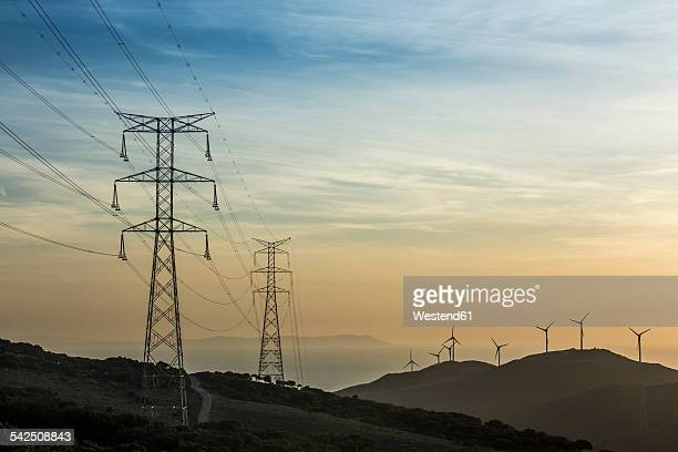 Spain, Andalusia, Tarifa, Wind farm and power pylons in the evening light