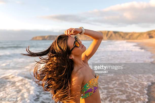 Spain, Asturias, beautiful young woman on the beach at sunset