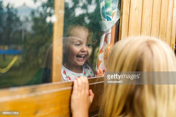 Spain, Asturias, Gijon, Little girls playing through a glass window