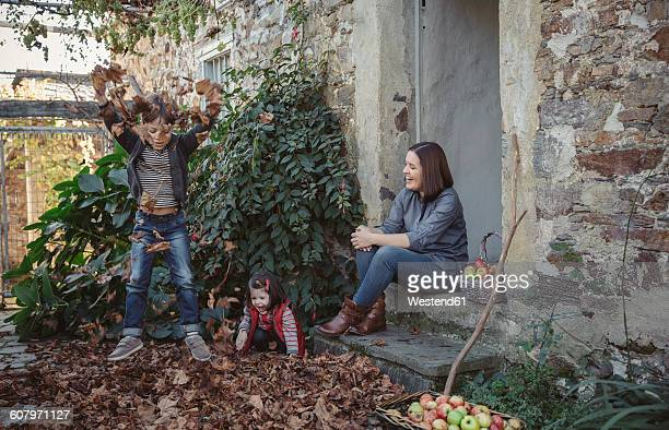 Spain, Asturias, woman sitting at entrance of country house watching her childs playing with autumn leaves