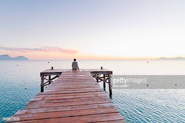 Spain, Balearic Islands, Majorca, one teenage boy sitting on a jetty in the morning