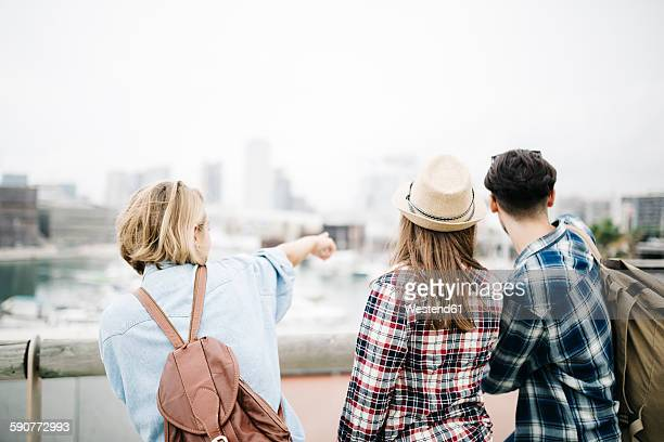 Spain, Barcelona, back view of three friends standing side by side pointing on something