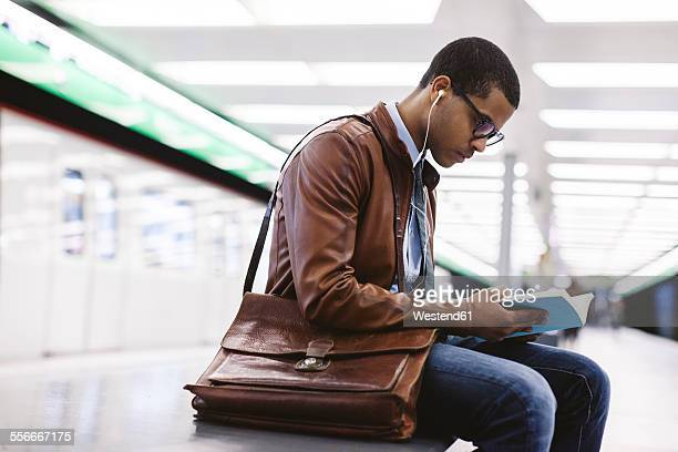 Spain, Barcelona, businessman sitting at underground station platform with book