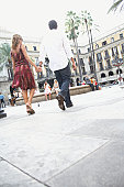 Spain, Barcelona, couple holding hands in Placa Real, rear view