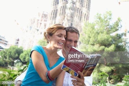 Spain, Barcelona, couple reading city guide near Sagrada Familia : Stock Photo