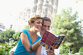 Spain, Barcelona, couple reading city guide near Sagrada Familia