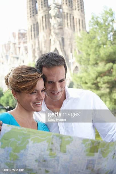 Spain, Barcelona, couple reading map near Sagrada Familia, close-up