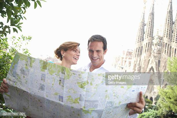 Spain, Barcelona, couple reading map near Sagrada Familia, laughing