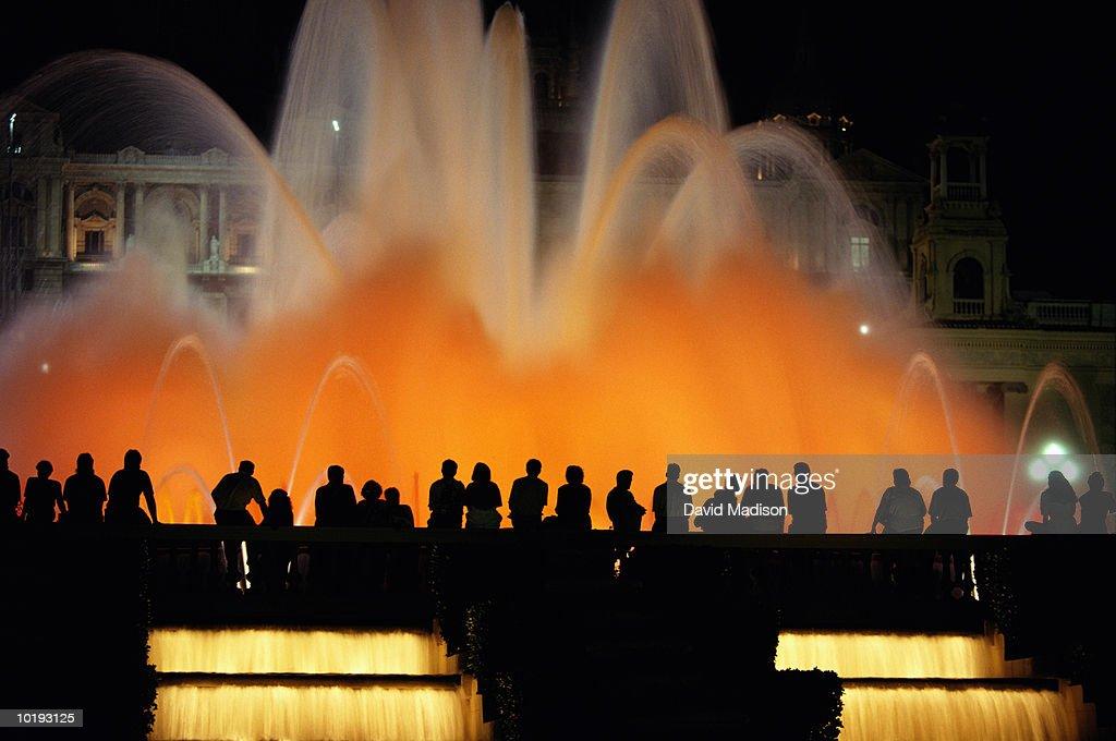 Spain, Barcelona, Plaza de Catalunya, spectators watching illuminated
