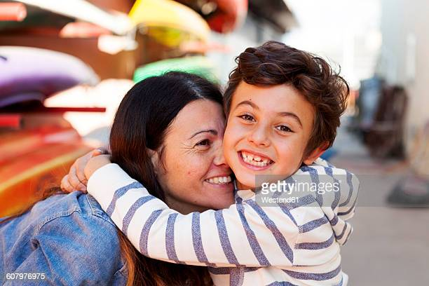 Spain, Barcelona, portrait of happy little boy hugging his mother