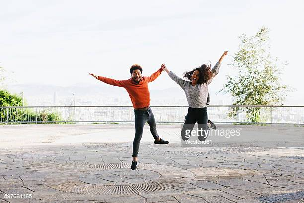 Spain, Barcelona, portrait of happy young couple jumping in the air on view terrace
