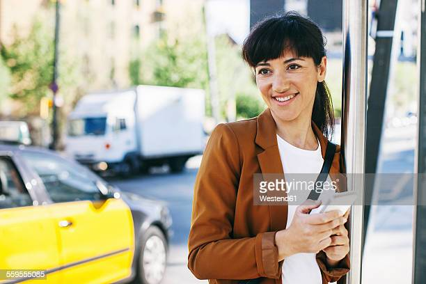 Spain, Barcelona, portrait of smiling businesswoman with smartphone waiting at the bus stop