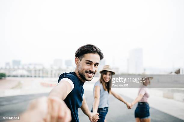 Spain, Barcelona, portrait of smiling young man holding hands with his friends